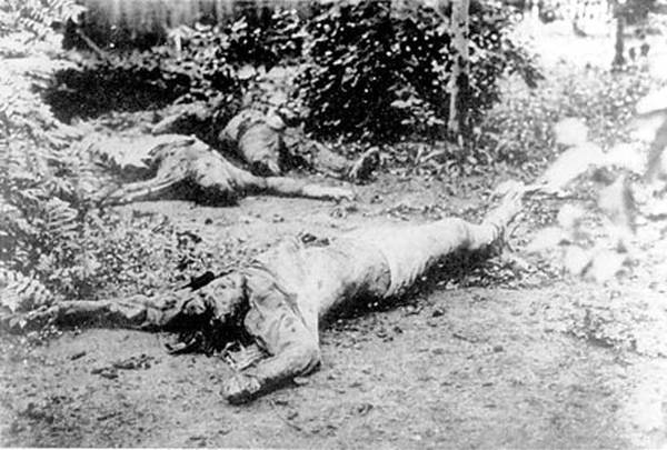 Courtyard scene in Kharkov The corpse of I. Ponomarenko. The right hand has been severed and across the chest deep cuts. In the background can be seen a further two corpses.