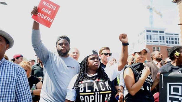 A hater black raises fist as the hater mob trmaples upon White Rights (Image:Scott Eisen/Getty Images)